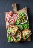 快餐板-熏火腿,橄榄,烤了无盐干酪在黑暗的背景,顶视图的菠菜三明治 地中海样式快餐, a 免版税图库摄影