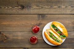快餐概念 做新热狗和家 热狗的在蕃茄sause附近的小圆面包用freid香肠和蓬蒿在黑暗 免版税图库摄影