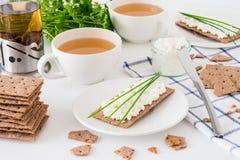 快餐用新鲜的茶和黑麦酥脆面包瑞典薄脆饼干用酸奶干酪,装饰用稀薄的葱,在白色backgr 免版税库存图片