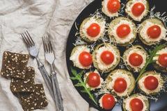 快餐用茄子、乳酪和在一个黑色的盘子供应的西红柿 在视图之上 免版税库存图片