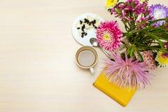 快餐用酸奶干酪和咖啡在桌上与翠菊在花瓶和一个黄色笔记薄 免版税库存照片