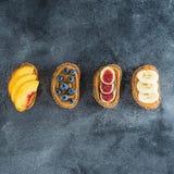 快餐用面包、花生酱、新鲜水果和莓果 健康概念的食物 平的位置,顶视图 图库摄影