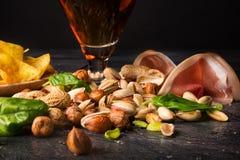 快餐的构成特写镜头在刷新的酒精饮料旁边的 啤酒和开胃菜在黑背景 免版税库存图片
