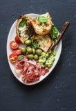 快餐碗-熏火腿,橄榄,西红柿,鲕梨垂度,烤了无盐干酪在黑暗的背景,顶视图的菠菜三明治 免版税图库摄影