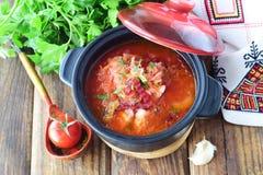 快餐 蔬菜汤用德国泡菜,甜菜根,红萝卜,葱,在一个黑罐的蕃茄在木背景 免版税库存图片