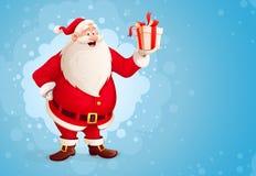 快活的圣诞老人拿着在箱子的圣诞节礼物 免版税库存照片