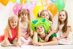 快活的孩子和小丑在生日 免版税图库摄影