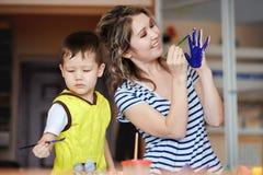 快活的童年,使用与他的母亲的一个小男孩,画,在棕榈的油漆 库存图片