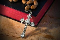 念珠小珠和圣经在木表上 免版税库存图片