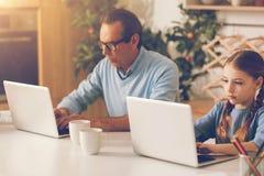 忽略在家研究膝上型计算机的父亲和女儿 库存图片