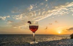 忽略海饮料的红色鸡尾酒在日落库拉索岛景色 免版税图库摄影