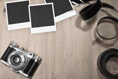 怀乡在木背景的概念空白立即照片框架与与影片小条和拷贝空间的老减速火箭的葡萄酒照相机 免版税库存图片