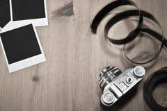 怀乡在木背景的概念空白立即照片框架与与影片小条和拷贝空间的老减速火箭的葡萄酒照相机 免版税图库摄影