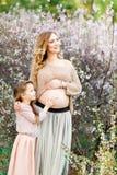 怀孕、人们和母性概念-走在公园的愉快的怀孕的亚裔妇女 免版税库存图片