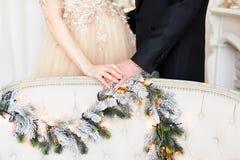 怀孕、寒假和人概念-接近握手的愉快的夫妇在圣诞节 免版税库存照片