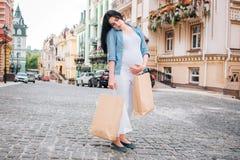 怀孕、母性、人们和期望概念-接近有购物袋的孕妇在城市街道 库存图片