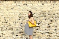 怀孕、母性和愉快的未来母亲概念-城市游览的孕妇对砖墙 库存照片