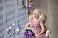 怀孕、母性和愉快的未来母亲概念-通风紫罗兰色礼服的孕妇有反对五颜六色的花束花的 库存照片
