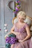 怀孕、母性和愉快的未来母亲概念-通风紫罗兰色礼服的孕妇有反对五颜六色的花束花的 免版税库存图片
