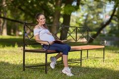 怀孕书的公园坐妇女年轻人 库存照片