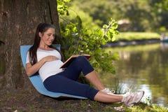 怀孕书的公园坐妇女年轻人 图库摄影