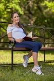 怀孕书的公园坐妇女年轻人 免版税库存照片