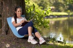怀孕书的公园坐妇女年轻人 免版税图库摄影