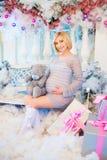 怀孕和圣诞节、人们和期望概念-接触她的腹部的愉快的孕妇 免版税库存照片