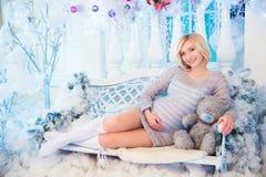 怀孕和圣诞节、人们和期望概念-接触她的腹部的愉快的孕妇 免版税库存图片