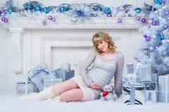 怀孕和圣诞节、人们和期望概念-接触她的腹部的愉快的孕妇 免版税图库摄影