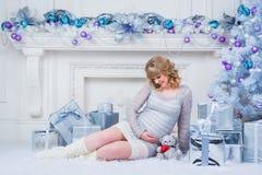 怀孕和圣诞节、人们和期望概念-接触她的腹部的愉快的孕妇 库存图片