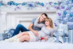 怀孕和圣诞节,年轻夫妇在圣诞树的背景等待 图库摄影