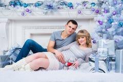 怀孕和圣诞节,年轻夫妇在圣诞树的背景等待 免版税图库摄影