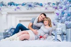 怀孕和圣诞节,年轻夫妇在圣诞树的背景等待 免版税库存图片