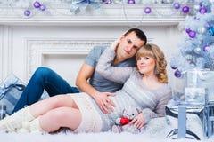 怀孕和圣诞节,年轻夫妇在圣诞树的背景等待 库存照片