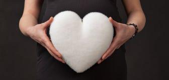怀孕心脏白色腹部手 图库摄影
