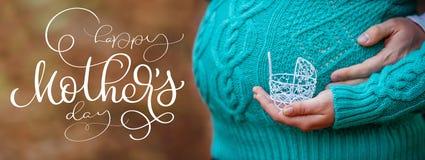 怀孕概念:鼓起用拿着小玩具婴儿推车的手在前面和文本愉快的母亲节 书法字法 库存图片