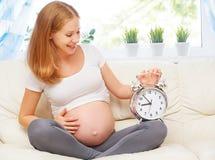 怀孕概念 有一个闹钟的愉快的孕妇在h 免版税库存照片