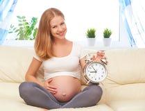 怀孕概念 有一个闹钟的愉快的孕妇在h 免版税库存图片