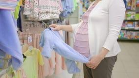 怀孕概念-选择蓝色婴儿紧身衣裤的孕妇在服装店 股票视频