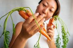 怀孕的亚洲妇女藏品束红萝卜 库存图片
