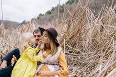 怀孕的享有生活的母亲、父亲和小女儿室外 库存图片