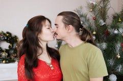 怀孕的亲吻,在圣诞节内部的愉快的年轻家庭画象的妻子和丈夫 库存图片