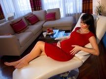 怀孕的休息的沙发妇女 免版税库存图片