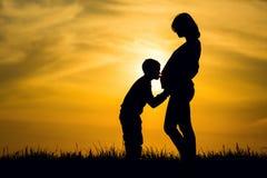 怀孕的剪影和她的儿子 库存图片