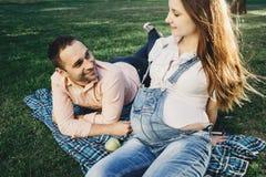 怀孕的夫妇在公园一起享受时间 免版税库存照片