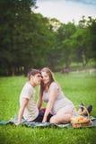 怀孕的夫妇坐的草 库存照片