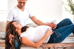 怀孕的夫妇拥抱和举行怀孕的腹部 免版税库存照片