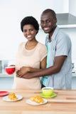 怀孕的夫妇食用早餐在厨房 免版税库存照片