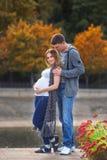 怀孕的夫妇-与花的拥抱在河附近 免版税库存照片